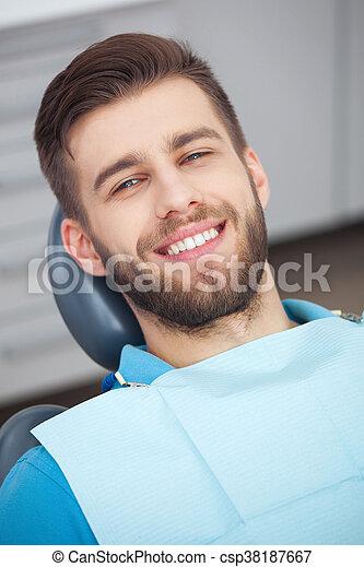 Portrait of happy patient in dental chair. - csp38187667