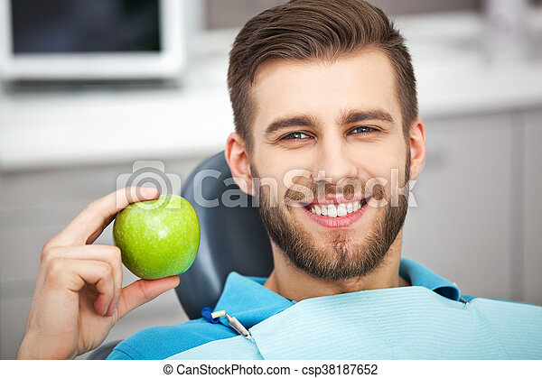Portrait of happy patient in dental chair with green apple. - csp38187652