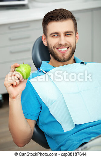 Portrait of happy patient in dental chair with green apple. - csp38187644