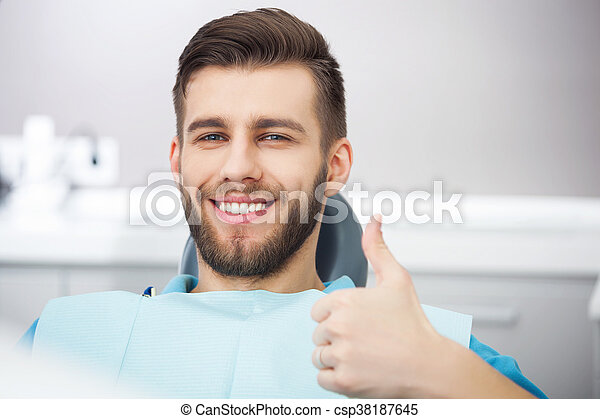 Portrait of happy patient in dental chair. - csp38187645