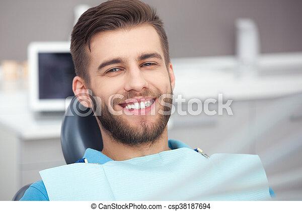 Portrait of happy patient in dental chair. - csp38187694