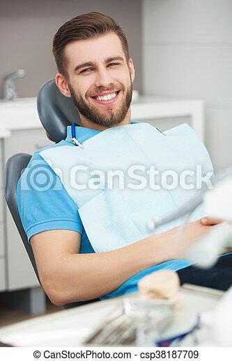Portrait of happy patient in dental chair. - csp38187709