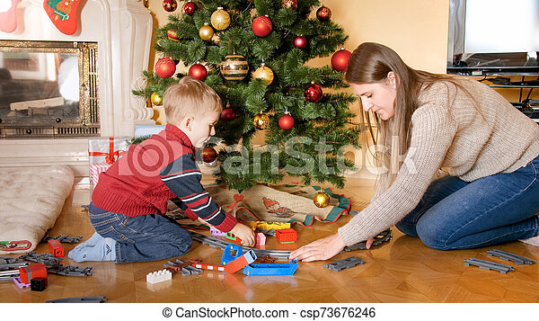 Portrait of happy smiling little boy with mother building railroad and playing with toy train on floor under Christmas tree - csp73676246