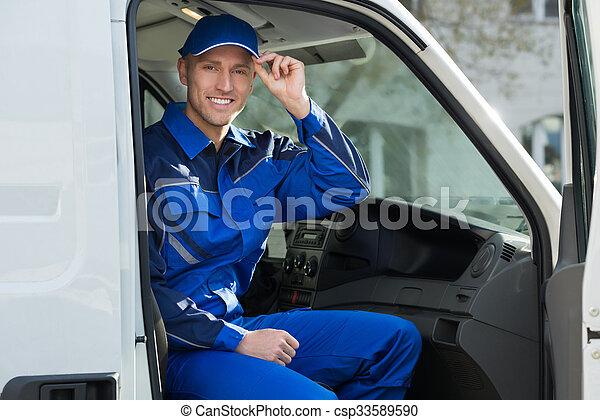 Portrait Of Happy Technician Sitting In Van - csp33589590
