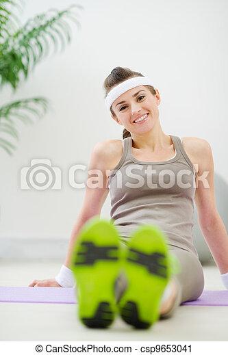 Portrait of happy woman in sportswear sitting on floor - csp9653041