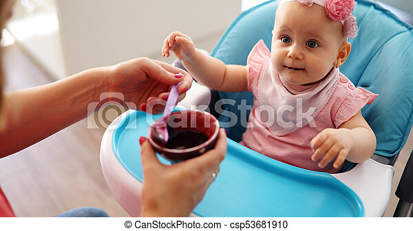 Portrait Of Happy Young Baby In High Chair being fed - csp53681910