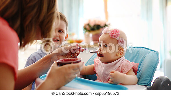 Portrait Of Happy Young Baby In High Chair being fed - csp55196572