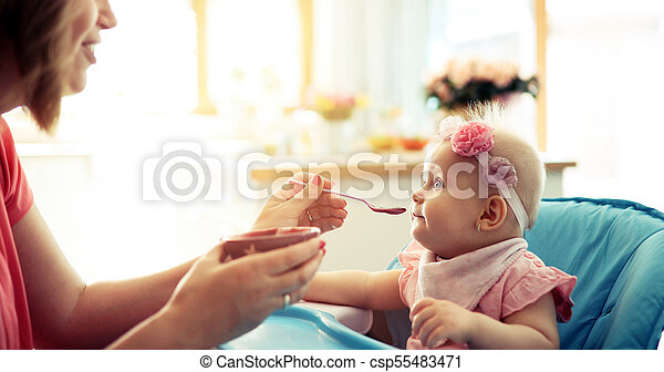 Portrait Of Happy Young Baby In High Chair being fed - csp55483471