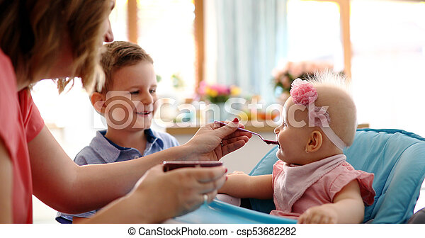 Portrait Of Happy Young Baby In High Chair being fed - csp53682282