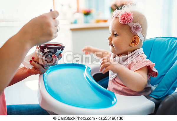 Portrait Of Happy Young Baby In High Chair being fed - csp55196138