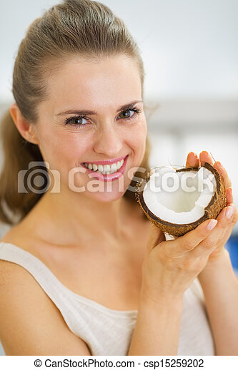 Portrait of happy young woman showing coconut - csp15259202
