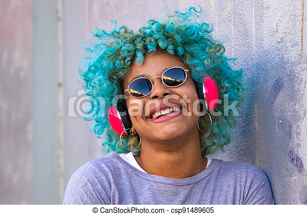 portrait of hispanic afro american woman with headphones and mobile phone smiling on the street - csp91489605
