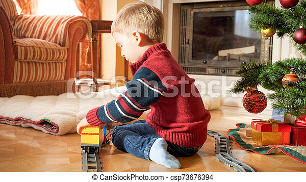 Portrait of little 3 years old boy sitting next to Christmas tree and playing with toy railroad. Child receiving presents and toys on New Year or Xmas - csp73676394