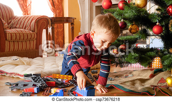 Portrait of little boy playing with toy train and railways on floor under Christmas tree - csp73676218