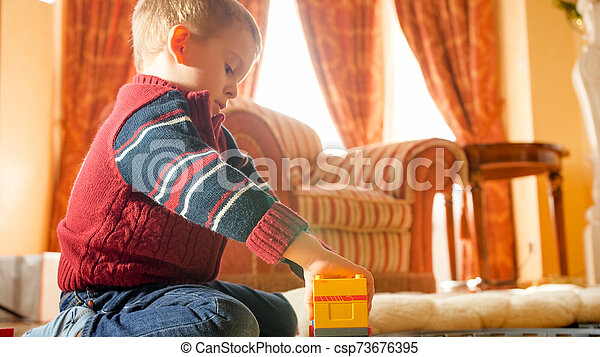 Portrait of little boy playing with toys on wooden floor at living room against big window - csp73676395