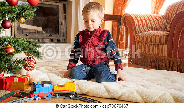Portrait of little boy sitting on floor and playing with toy railroad that Santa gave him for Christmas. Child receiving presents and toys on New Year or Xmas - csp73676467