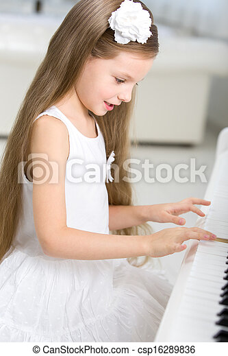 Portrait of little musician in white dress playing piano - csp16289836