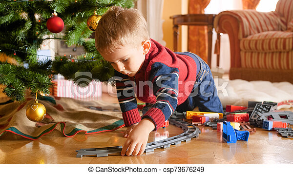 Portrait of little toddler boy building railway and playing with toy train under Christmas tree - csp73676249