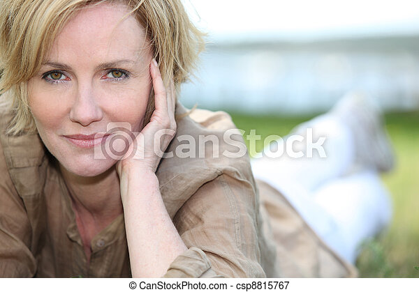 portrait of magnificent mature blonde lying on grass - csp8815767