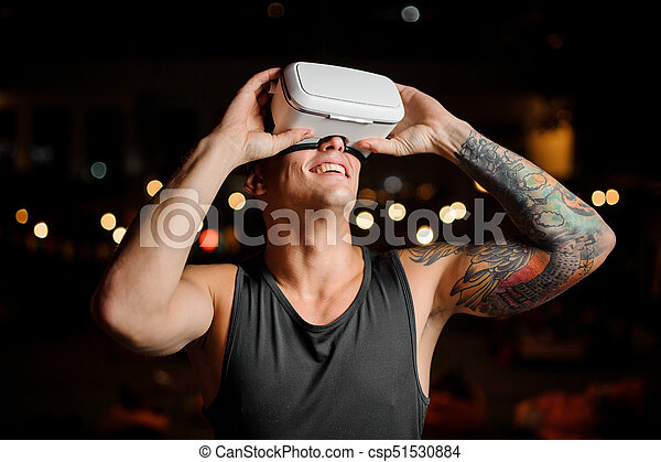 Portrait of man and vr glasses playing an exciting game. Concept of the future. - csp51530884