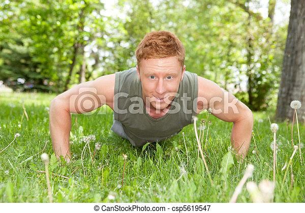 Portrait of man doing a push up - csp5619547
