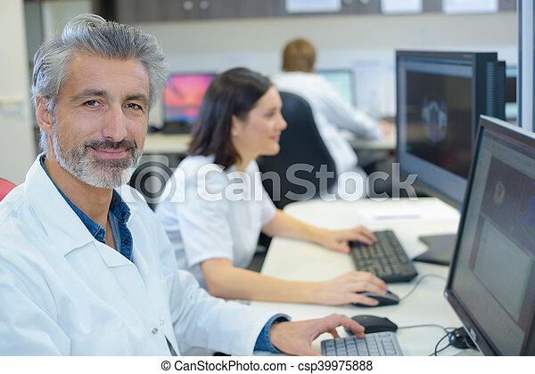 Portrait of man in white coat using computer - csp39975888