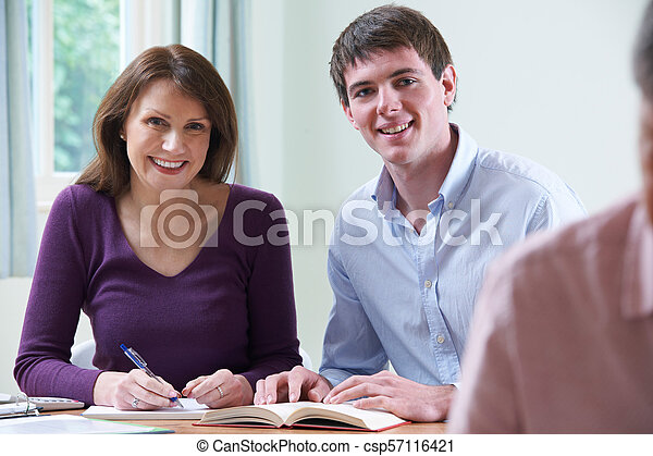 Portrait Of Mature Woman With Tutor In Adult Education Class - csp57116421