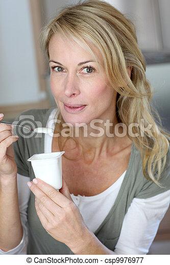 Portrait of middle-aged woman eating yogurt - csp9976977