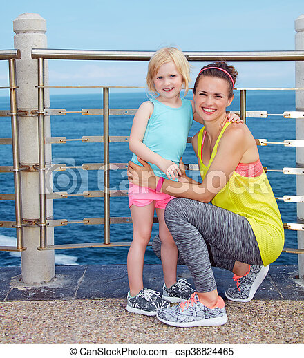 Portrait of mother and child in fitness outfit on embankment - csp38824465