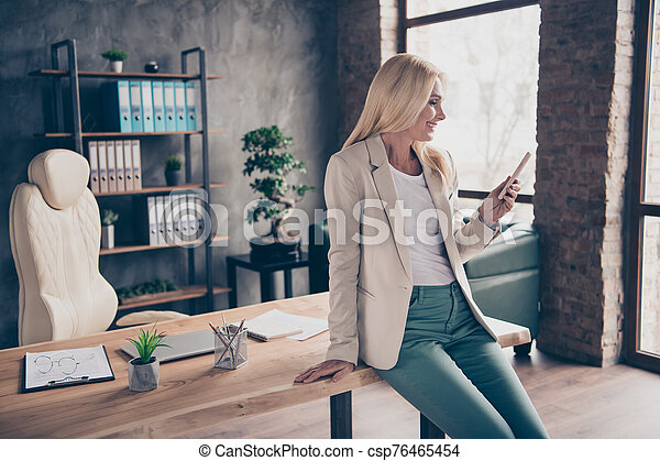 Portrait of positive confident cool blonde hair middle aged businesswoman use her cellphone type messages communicate chatting with work partners investors sit on wooden table in office workplace - csp76465454