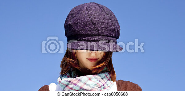 Portrait of red-haired girl with scarf and purple cap on blue sky background. - csp6050608