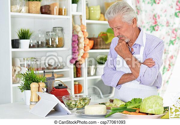 Portrait of senior man preparing dinner in kitchen - csp77061093