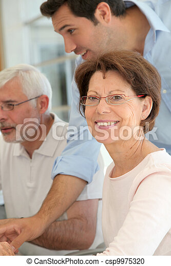 Portrait of senior woman attending computing training - csp9975320