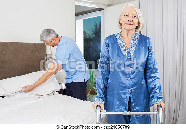 Portrait Of Senior Woman With Walking Frame At Nursing Home - csp24650789