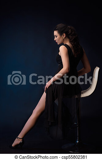 portrait of sensual woman on black dress sitting in a chair - csp55802381