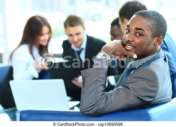 Portrait of smiling African American business man with executives working in background - csp10695598
