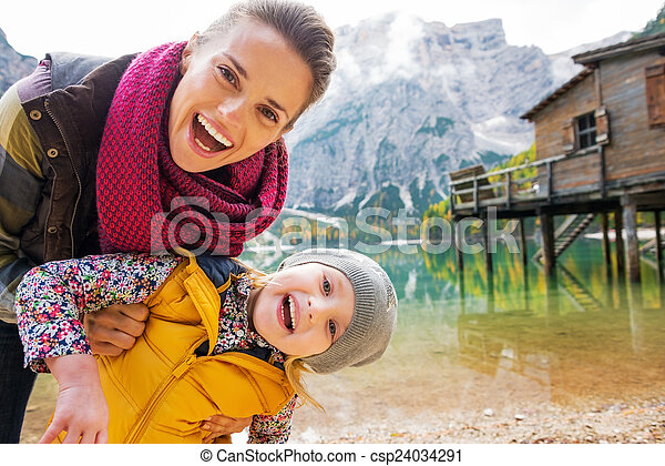 Portrait of smiling mother and baby on lake braies in south tyro - csp24034291