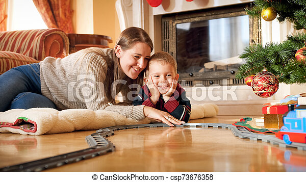 Portrait of smiling mother with her little son lying on wooden floor under Christmas tree and playing with toy railroad. Child receiving presents and toys on New Year or Xmas - csp73676358