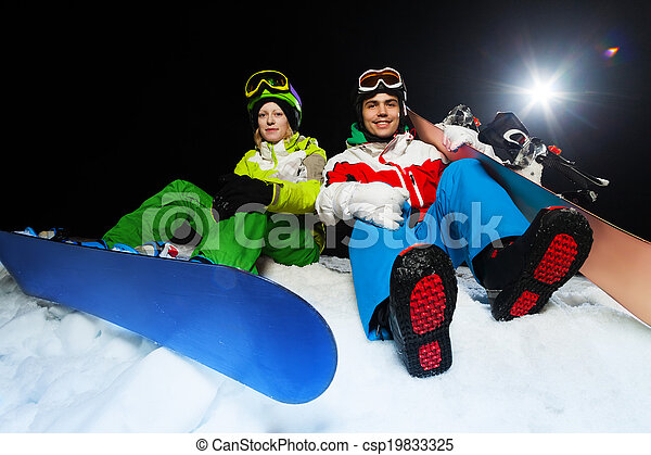 Portrait of smiling snowboarders at night - csp19833325