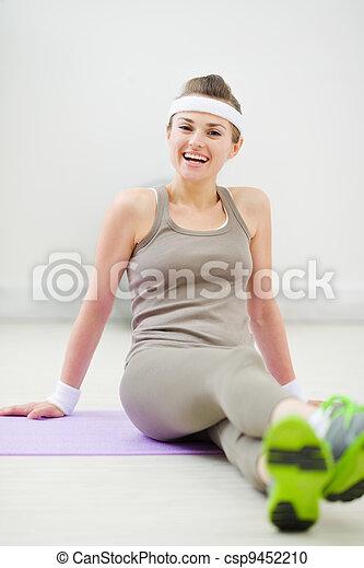 Portrait of smiling woman in sportswear sitting on floor - csp9452210