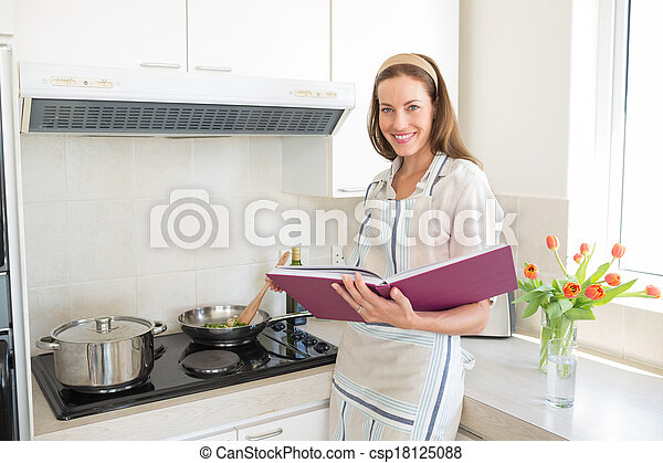 Portrait of smiling woman preparing food in kitchen - csp18125088