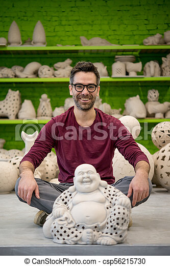 Portrait of Smiling Young Ceramist in the Bright Modern Ceramic Workshop Sitting Next to Sculpture. Small Business Concept. - csp56215730