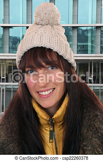 Portrait of smiling young woman in winter in town - csp22260378