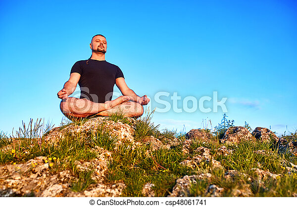Portrait of the man sitting on a rock in the lotus position against blue sky. - csp48061741