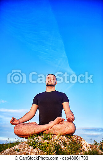 Portrait of the man sitting on a rock in the lotus position against blue sky. - csp48061733