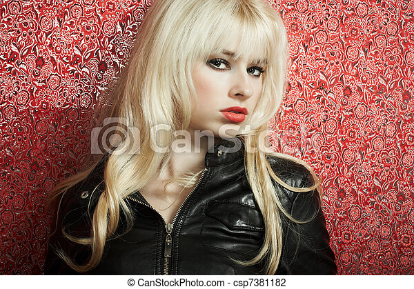 Portrait of the young blonde woman on a red background - csp7381182