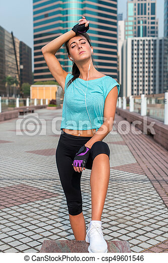 Portrait of tired young fitness woman taking a break from working-out, wiping sweat from her forehead, listening to music. Female athlete resting after exercising outdoors on city street - csp49601546