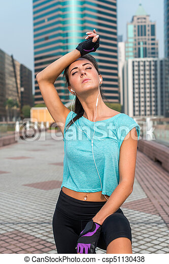 Portrait of tired young fitness woman taking a break from working-out, wiping sweat from her forehead, listening to music. Female athlete resting after exercising outdoors on city street - csp51130438
