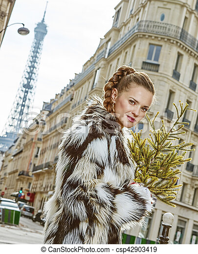 Boiling hot trendy winter in Paris. Portrait of trendy woman with Christmas tree in Paris, France