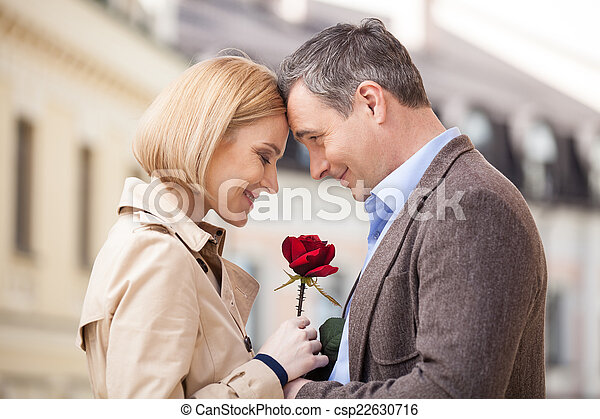 Portrait of two people holding rose and smiling. adult man giving red flower to blond woman outside - csp22630716